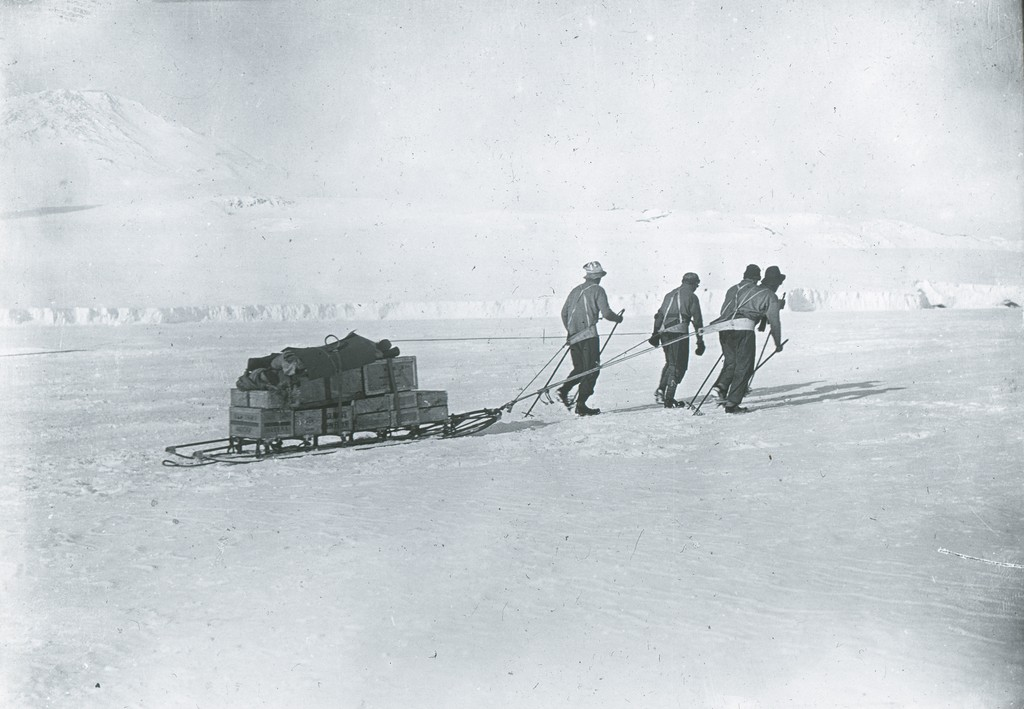 four men pulling a sled away from the ship in british antarctic expedition 1910