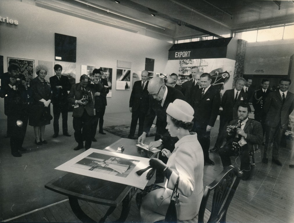 Photograph of the Queen signing an image of herself, May 1969 DUNIH 2017.16.2.32