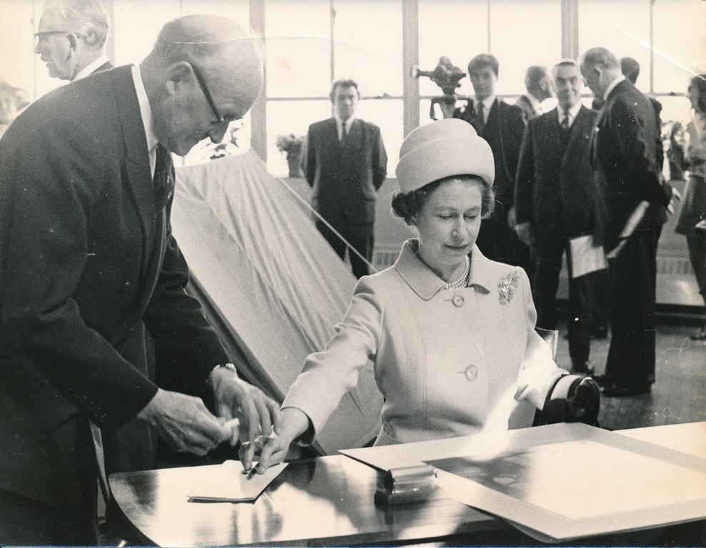Photograph of the Queen signing an image of herself, May 1969 DUNIH 2017.16.2.33