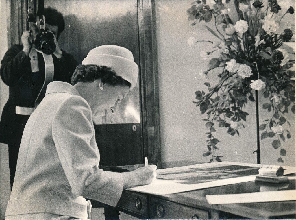 Photograph of the Queen signing an image of herself, May 1969 DUNIH 2017.16.2.34