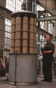 Image of Jute bobbins being lowered into a dyeing vat (pre treatment) DUNIH 2006.1.20.6