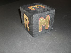 Image of Cube painted black with stencilled letters in gold and red DUNIH 2011.1.81